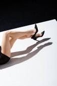 Fotografie Ausgeschnittene Ansicht einer Frau in schwarzem Kleid und Fersen, die auf weißer Oberfläche auf schwarzem Hintergrund liegt