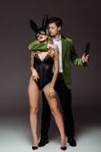 Dominanter Mann umarmt sexy Frau in Hasenmaske und hält Prügel-Paddel auf grauem Hintergrund
