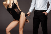 Fotografie Cropped view of man holding spanking paddle near sexy woman in bodysuit isolated on grey