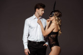 Fotografie Seductive girl in erotic rabbit mask touching handsome man isolated on grey