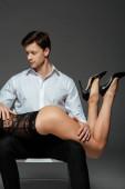 Fotografie Sexy Frau auf Knien liegend schöner Mann sitzt auf Stuhl auf grauem Hintergrund