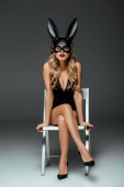 Photo Sexy woman in rabbit mask sitting on chair on grey background
