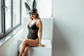 Photo Sexy blonde woman in rabbit mask looking at camera while sitting on white cube near window