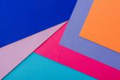 abstraktní geometrické pozadí s oranžovým, růžovým, modrým a fialovým papírem