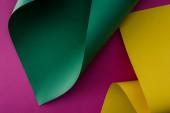 zelené a žluté barevné papírové víří na fialovém pozadí