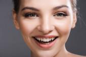 zblízka šťastné mladé ženy s make-upem s úsměvem a při pohledu na kameru izolované na šedé