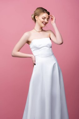 Happy young bride in white wedding dress standing with hand on hip isolated on pink stock vector