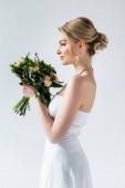 boční pohled krásné nevěsty drží svatební květiny na bílém