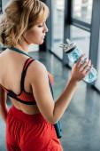 atraktivní sportovkyně drží sportovní láhev s vodou v tělocvičně