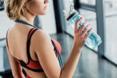 oříznutý pohled na sportovkyni držící sportovní láhev s vodou v tělocvičně