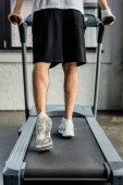 Ausgeschnittene Sicht auf Sportler in Turnschuhen beim Training auf dem Laufband