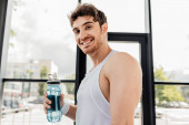 happy sportsman holding sports bottle with water