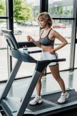 Attraktive Sportlerin läuft im Fitnessstudio auf Laufband