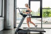 Fotografie Seitenansicht einer attraktiven Sportlerin, die im Fitnessstudio auf dem Laufband läuft