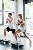 sportovní pár se zaťatými rukama dělá výpady cvičení na platformách kroku