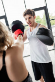 selective focus of man in boxing pads screaming near girl training in sports center