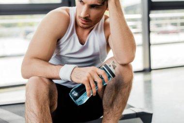 Yorgun sporcu elinde su şişesi tutuyor.