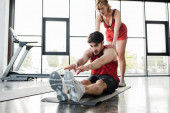 Fotografie beautiful sportswoman touching athletic sportsman stretching on fitness mat