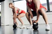 Fotografie selektivní zaměření sportovního páru cvičení s těžkými činkami v tělocvičně
