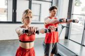 selektivní zaměření sportovního páru cvičení s činkami v tělocvičně