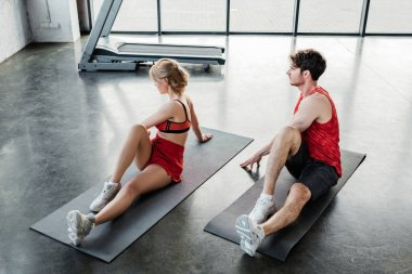 sport couple in sportswear stretching on fitness mats in gym