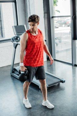 Strong man holding heavy dumbbell near treadmill in sports center stock vector