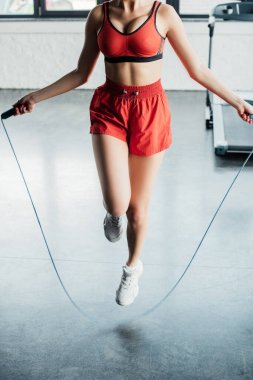 Cropped view of sportive girl jumping while holding skipping rope in gym stock vector