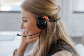 side view of cheerful operator in headset smiling in office
