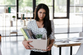 upset and dismissed manager holding box with folders and documents