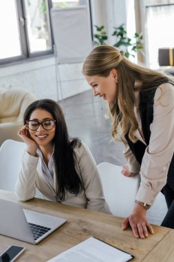 Selective focus of happy businesswoman standing near attractive coworker in glasses and looking at laptop stock vector