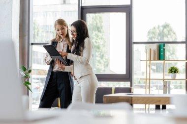 Selective focus of attractive businesswomen looking at clipboard stock vector