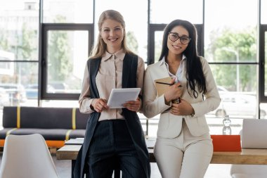 Happy businesswoman holding digital tablet near beautiful coworker in glasses with notebook and pen stock vector