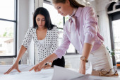 selective focus of businesswomen looking at blueprints in office