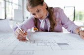 Photo selective focus of beautiful businesswoman drawing blueprints in office