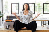 beautiful businesswoman with closed eyes meditating on table in office