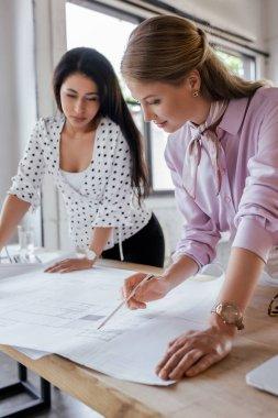 Selective focus of attractive businesswomen looking at blueprints in office stock vector