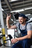 šťastný mechanik v čepici ukazující rockovou značku a držící papírový kelímek v dílně