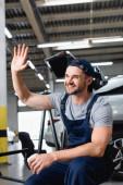 fröhlicher Mechaniker mit Mütze, winkender Hand und Pappbecher in der Autowerkstatt