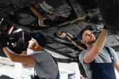 Nízký anděl pohled na hezké mechaniky v čepice upevnění auta v čerpací stanici