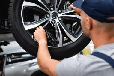 Selective focus of technician touching wheel disk while fixing car stock vector