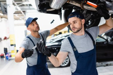 Selective focus of mechanic holding flashlight and taking wrench while coworker looking at car in service station stock vector