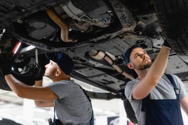 Low angel view of handsome mechanics in caps fixing car in service station stock vector