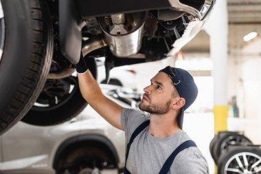 Selective focus of handsome mechanic in cap fixing car stock vector