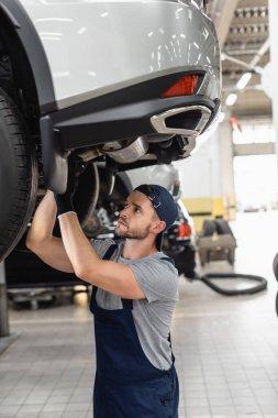 Selective focus of handsome mechanic in uniform and cap fixing car stock vector