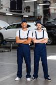 veselá mechanika v uniformě a čepice stojící se zkříženýma rukama v autoservisu