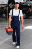 schöner Mechaniker in Uniform und Mütze mit Werkzeugkiste in der Tankstelle