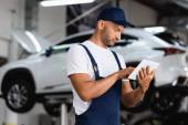 schöner Mechaniker in Overalls und Mütze mit digitalem Tablet im Autoservice