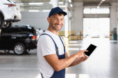 happy mechanic in overalls and cap pointing with finger at digital tablet with blank screen in car service