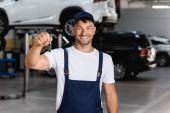 fröhlicher Mechaniker in Overalls und Mütze mit Autoschlüssel