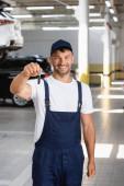glücklicher Mechaniker in Uniform und Mütze mit Autoschlüssel